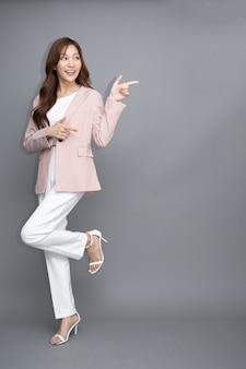 Aziatische zakenvrouw glimlachend en wijzende vinger naar lege kopieerruimte geïsoleerd op een grijze achtergrond