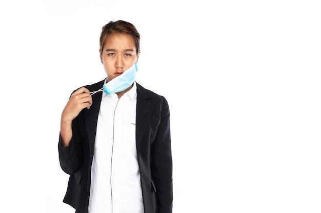 Aziatische zakenvrouw in ernstig gezicht opstijgen chirurgisch gezichtsmasker met één hand in zwart jasje, kijk naar camera, geïsoleerd op witte achtergrond, coronavirus, covid19