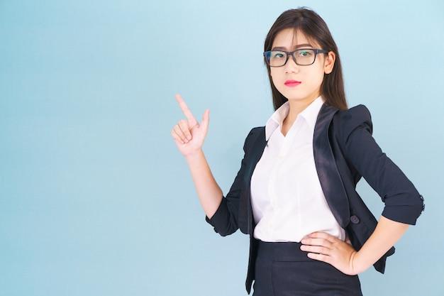 Aziatische zakenvrouw in pak met vinger omhoog op blauwe achtergrond