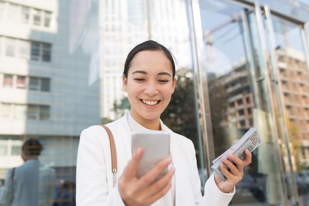 Aziatische zakenvrouw is blij omdat ze veel geld heeft verdiend