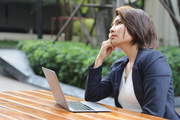Aziatische zakenvrouw kijkt rond voor inspiratie van het werken aan een openbaar park om een goed idee te krijgen met de oude omgeving met laptop en draadloze internettechnologie