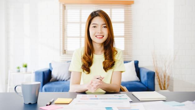 Aziatische zakenvrouw met behulp van computer laptop praten met collega's over plan in videogesprek vergadering tijdens het werken vanuit huis in de woonkamer. zelfisolatie, sociale afstand nemen, quarantaine voor coronavirus.