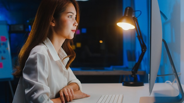 Aziatische zakenvrouw met behulp van computer praten met collega's over plan in videogesprek tijdens het werken vanuit huis in de woonkamer 's nachts. zelfisolatie, sociale afstand nemen, quarantaine voor coronaviruspreventie.