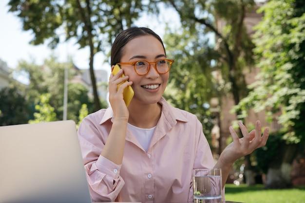 Aziatische zakenvrouw met een stijlvolle bril die op een mobiele telefoon praat
