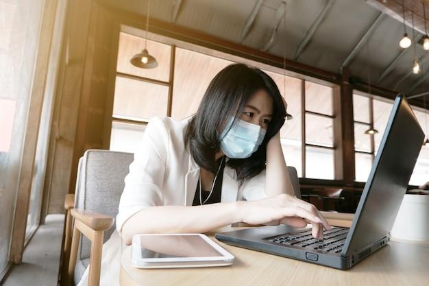 Aziatische zakenvrouw met masker die op laptop werkt