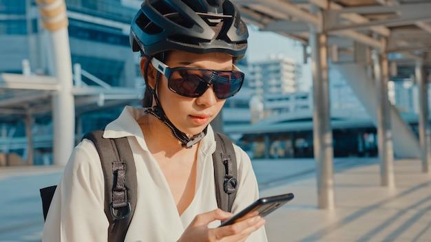 Aziatische zakenvrouw met rugzak met behulp van mobiele telefoon in stad straat gaan werken op kantoor.
