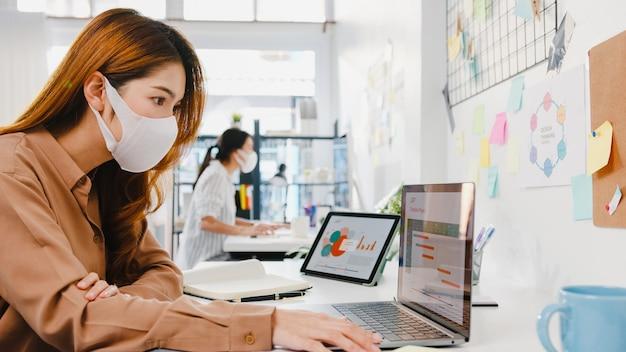 Aziatische zakenvrouw-ondernemer die een medisch gezichtsmasker draagt voor sociale afstand in een nieuwe normale situatie voor viruspreventie tijdens het gebruik van een laptop op het werk op kantoor.