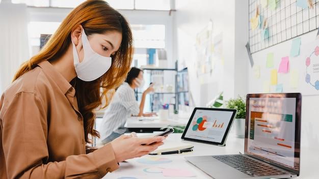 Aziatische zakenvrouw-ondernemer die gezichtsmasker draagt voor sociale afstand in een nieuwe normale situatie voor viruspreventie tijdens het gebruik van laptop en telefoon op het werk op kantoor.