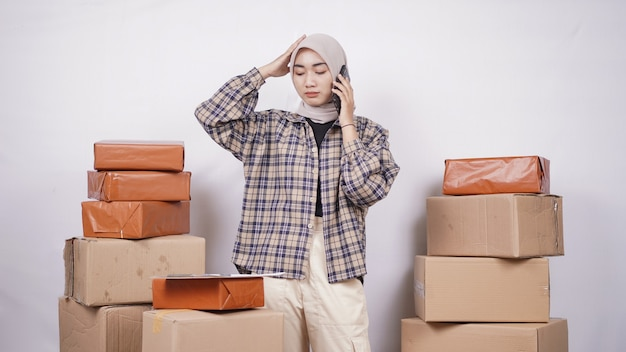 Aziatische zakenvrouw op telefoon gebaren verward geïsoleerd op witte achtergrond