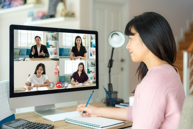 Aziatische zakenvrouw praten met haar collega's over plan in videoconferentie.