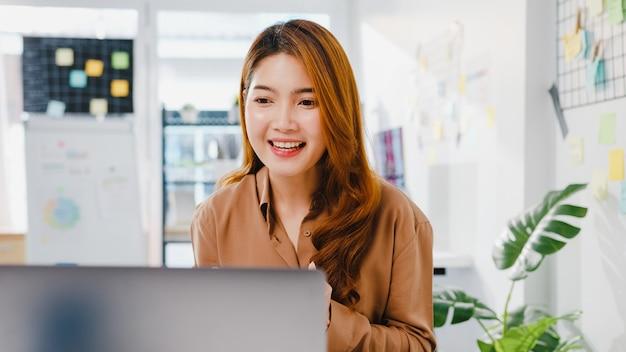Aziatische zakenvrouw sociale afstand in nieuwe normale situatie voor viruspreventie tijdens het gebruik van laptoppresentatie aan collega's over plan in videogesprek terwijl ze op kantoor werken.