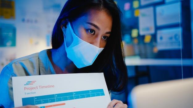Aziatische zakenvrouw sociale afstand nemen in nieuwe normale situatie voor preventie tijdens het gebruik van laptoppresentatie aan collega's over plan in videogesprek tijdens het werken op kantooravond. leven na het coronavirus.