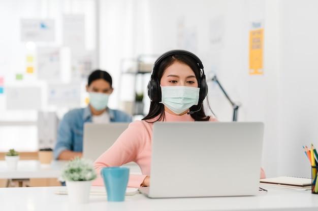 Aziatische zakenvrouw sociale afstand nemen in nieuwe normale situatie voor viruspreventie tijdens het gebruik van laptoppresentatie aan collega's over plan in videogesprek tijdens het werk op kantoor. leven na het coronavirus.