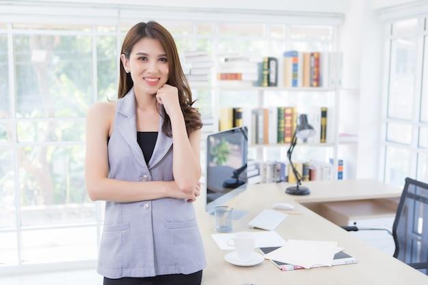 Aziatische zakenvrouw staat en glimlacht gelukkig op de werkplek. werk vanuit huis.