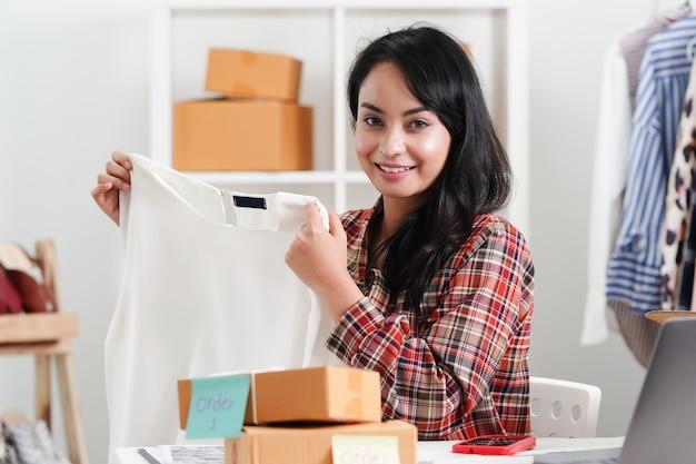 Aziatische zakenvrouw verkopen mode doek en kleding.
