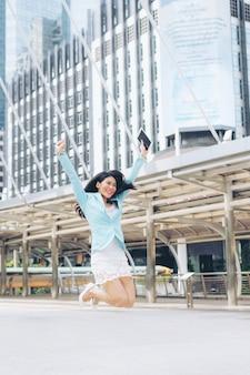 Aziatische zakenvrouw voelt gelukkig springen lucht