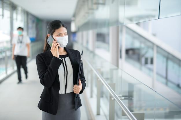Aziatische zakenvrouw wandelen met chirurgische masker gezicht bescherming lopen in menigten op de luchthaven