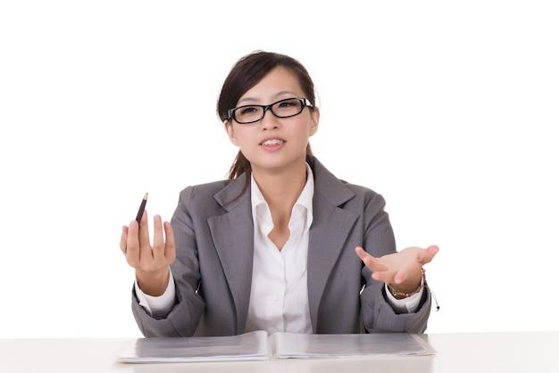 Aziatische zakenvrouw zitten en praten met je, studio-opname op een witte achtergrond.