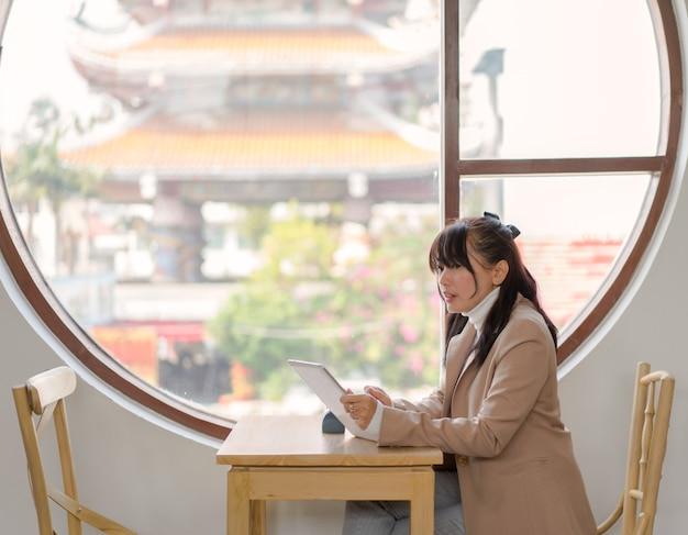 Aziatische zakenvrouw zitten met behulp van tablet voor bestelling en werken bij restaurant