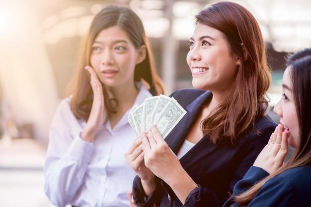 Aziatische zakenvrouwen met collega houden geld vast voor succes