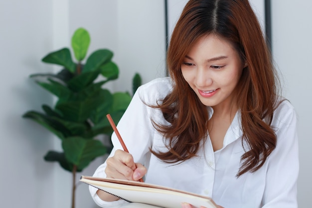 Aziatische zakenvrouwen schrijven marketinginformatie op in potloden.