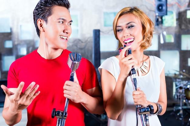 Aziatische zanger die lied in opnamestudio produceert
