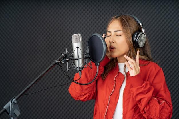 Aziatische zangeres vrouw in een opnamestudio met behulp van een studiomicrofoon met passie in muziekopnamestudio using