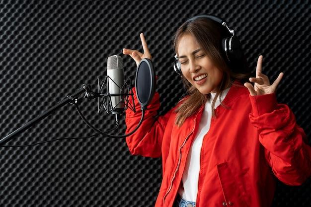 Aziatische zangeres vrouw in een opnamestudio met behulp van een studiomicrofoon met passie in muziekopnamestudio