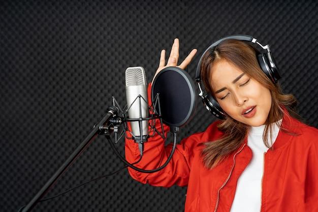 Aziatische zangeres vrouw in een opnamestudio met behulp van een studiomicrofoon