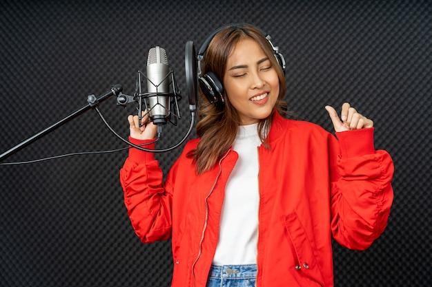 Aziatische zangeres vrouw in een opnamestudio met behulp van een studiomicrofoon Premium Foto