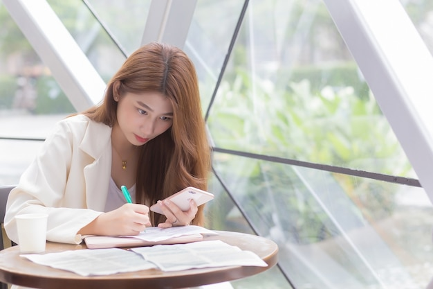 Aziatische zelfverzekerde vrouw draagt een crèmekleurig pak terwijl ze een smartphone gebruikt en iets schrijft