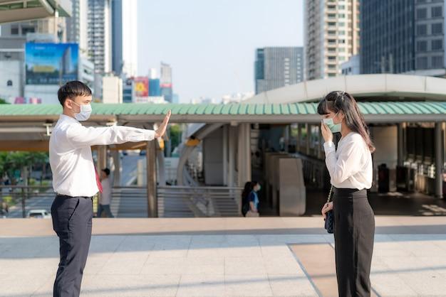 Aziatische zieke zakenvrouw hoest met masker en zakenman stopbord overhandigen hem om afstand te bewaren tegen covid-19-virussen en mensen die afstand houden voor infectierisico