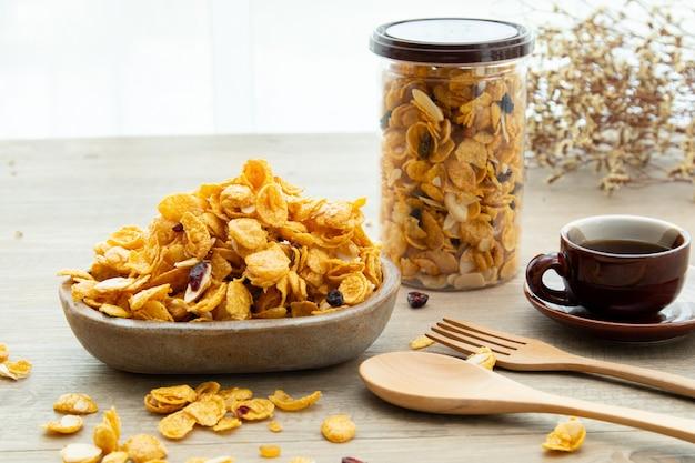 Aziatische zoete snacks, smakelijke gemengde cornflakes, noot, druif en karamel op houten achtergrond natuurlijk licht. verpakking van zoete snacks met een kopje thee en kopieerruimte. stickermodel voor logo