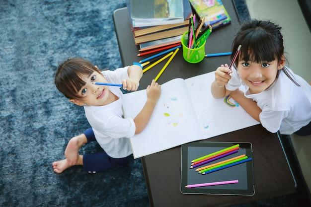 Aziatische zussen kijken naar de camera tijdens het tekenen