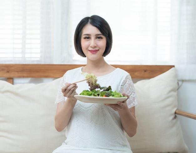 Aziatische zwangere vrouw die groene verse salade op bus houdt