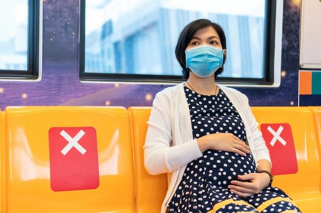 Aziatische zwangere vrouw die in gezichtsmasker door forenzentrein reizen te werken
