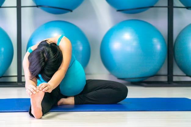 Aziatische zwangere vrouw die yoga in gymnastiek doet