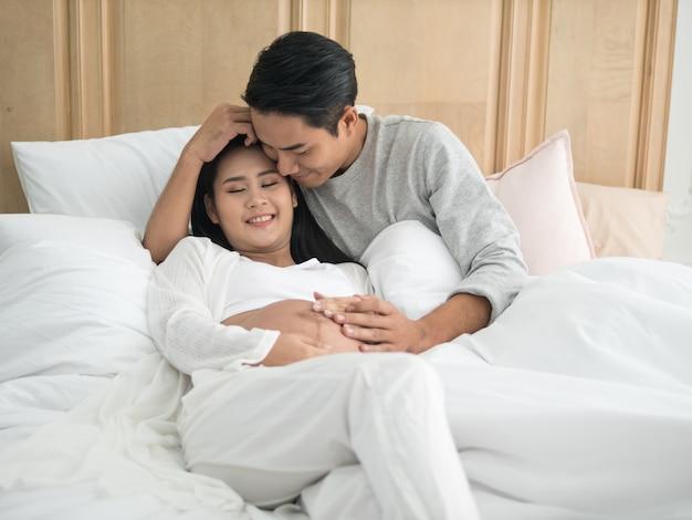 Aziatische zwangere vrouw en echtgenoot die op het bed leggen terwijl samen het doorbrengen van tijd.