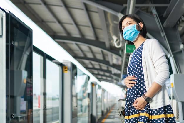 Aziatische zwangere vrouw in gezichtsmasker die forenzentrein wachten voor het reizen