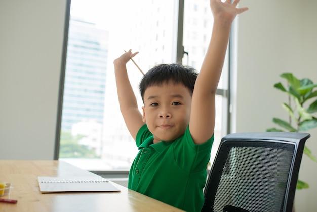 Azië kleine studentenjongen die thuis studeert en zijn huiswerk doet, op tafel, thuisonderwijs, denkactie