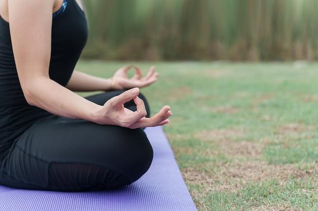 Azië mooi meisje beoefenen van yoga in de natuur, groene achtergrond