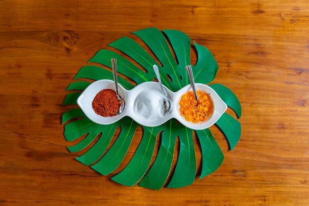 Azië-smaakstof in de kleine witte kom zoals azijn, suiker en chili voor een soort thaise noedels.