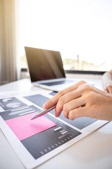 Azië vrouw hand met pen analyse van de grafiek met calculartor en laptop op het kantoor aan huis