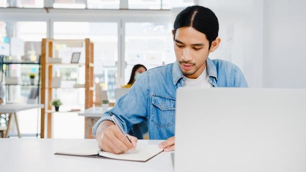 Azië zakenman sociaal distantiëren in nieuwe normale situatie voor viruspreventie met behulp van laptoppresentatie aan collega over plan in videogesprek tijdens het werk in thuiskantoor. levensstijl na coronavirus.