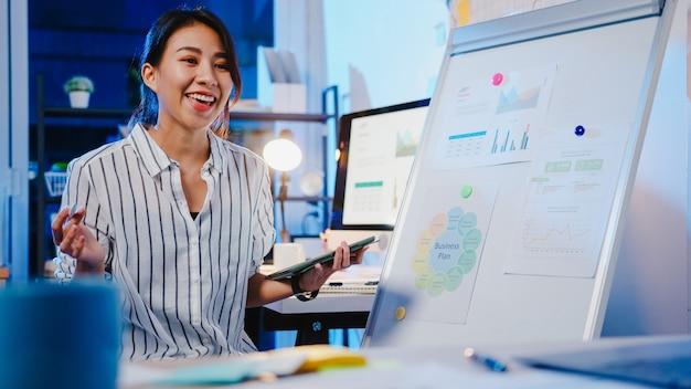 Azië zakenvrouw sociale afstand in het nieuwe normaal voor viruspreventie kijken naar camerapresentatie aan collega over plan in videogesprek tijdens het werk in kantoornacht.