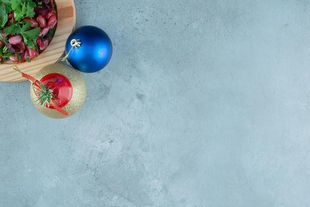 Azijn serveren op een houten schotel en twee kerstballen op marmer.