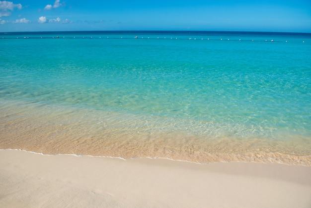 Azuurblauwe turquoise kalme zee, heldere blauwe lucht, zandstrand en vlakke horizon