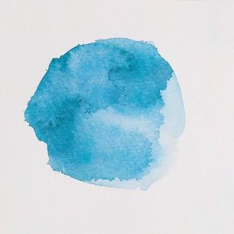Azuurblauwe verf in de vorm van een cirkel op wit papier