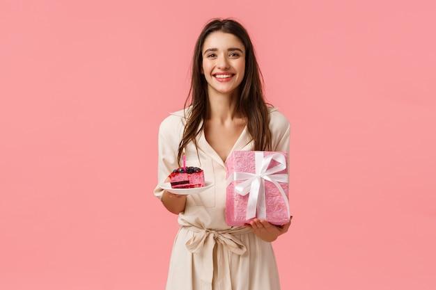 B-dag meisje voelt zich gelukkig en vrolijk, geniet van het vieren. aantrekkelijke blanke vrouw ontvangt cadeautjes, houden heerlijke stuk cake, verpakte aanwezig, vrolijk glimlachen, permanent roze