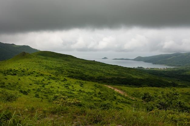 Baai van de zee vanaf de top van de heuvel van de bergachtige kust, zomerlandschap en zeegezicht bij bewolkt bewolkt weer.